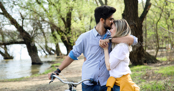 Young loving couple dating while riding bicycles in the city - Stock Photo - Images