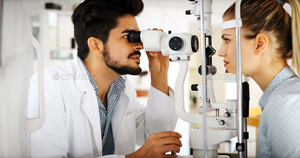 Attentive optometrist examining female patient on slit lamp - Stock Photo - Images
