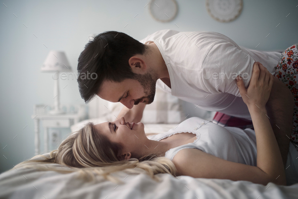 Beautiful couple being romantic and passionate in bed - Stock Photo - Images