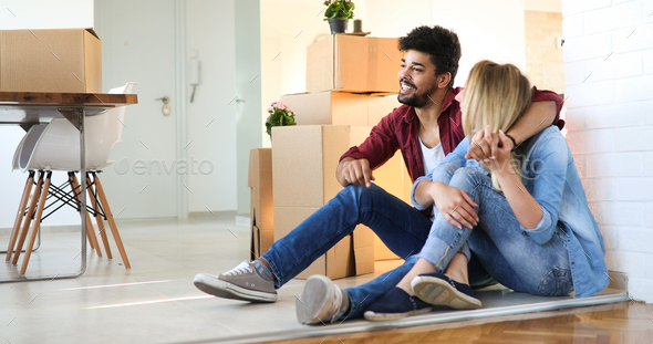 Young happy couple moving in new home and unpacking boxes - Stock Photo - Images