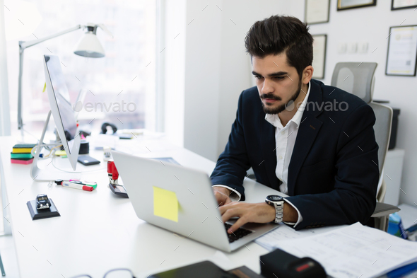 Portrait of young handsome working in office - Stock Photo - Images
