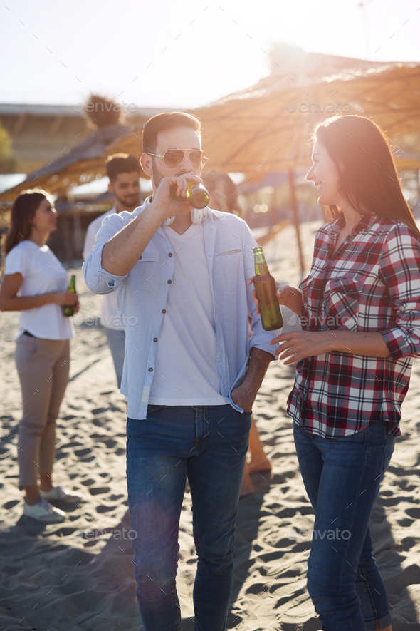 Happy couple smiling and drinking beer at beach - Stock Photo - Images