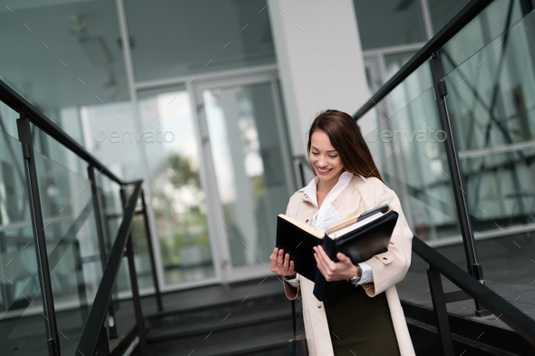 Beautiful and attractive businesswoman looking at files - Stock Photo - Images