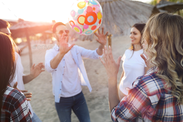 Group of young cheerful friends playing with ball - Stock Photo - Images