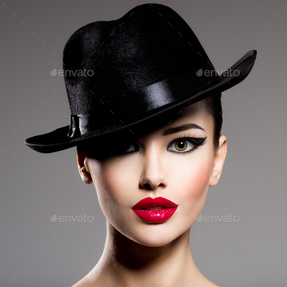 Сlose-up portrait of a woman in a black hat  with red lips - Stock Photo - Images