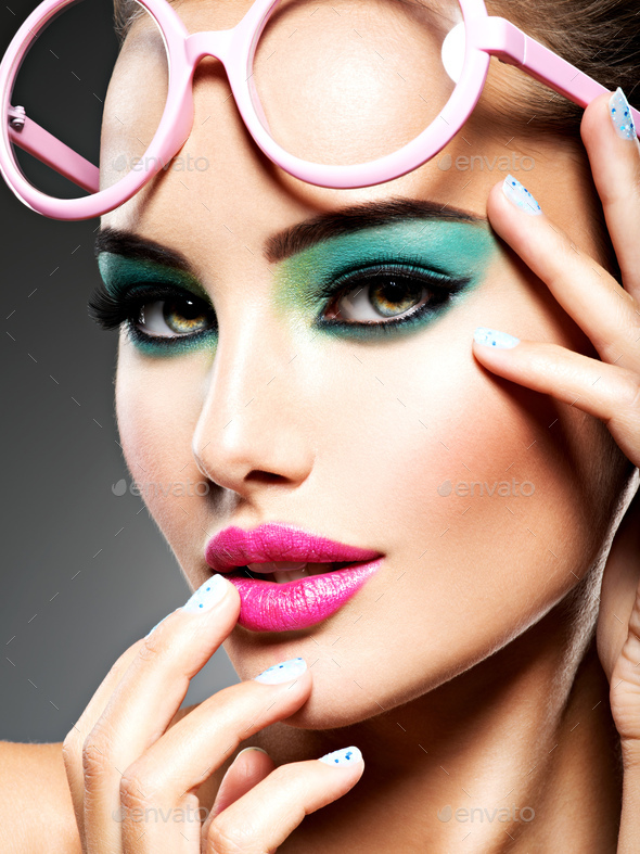 Beautiful Face of a woman with green vivid make-up of eyes - Stock Photo - Images