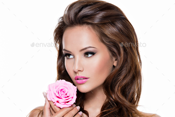 Face of a beautiful  woman with long brown hairs and pink flower - Stock Photo - Images