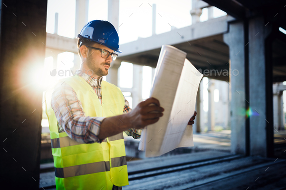 Architect holding rolled up blueprints at construction site - Stock Photo - Images