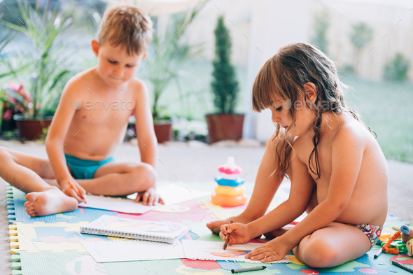 Little boy and girl drawing with crayons - Stock Photo - Images