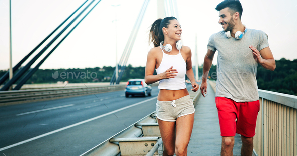 Athletic young cute couple jogging together outdoors - Stock Photo - Images