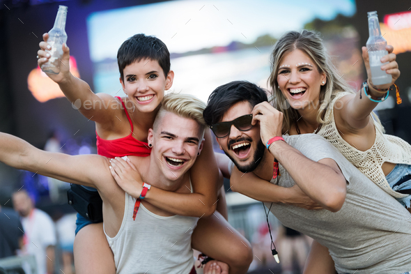 Happy friends having fun at music festival - Stock Photo - Images