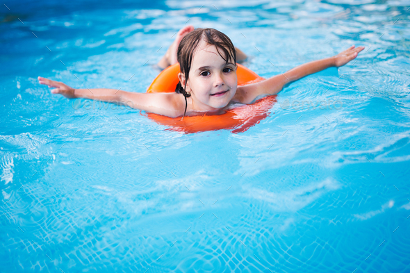 Little girl in swimming pool with float ring - Stock Photo - Images