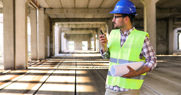 Male architect with blueprints using walkie-talkie - Stock Photo - Images