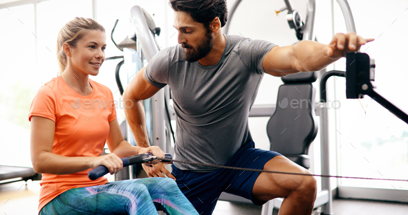 Young beautiful woman doing exercises with personal trainer - Stock Photo - Images