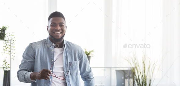 Portrait of smiling black guy with glasses in hands - Stock Photo - Images