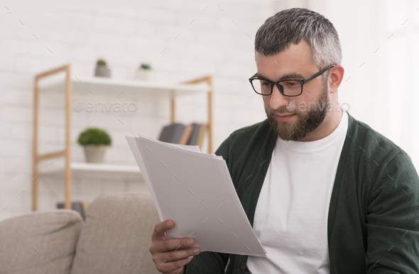 Concentrated man reading printed article, education at home - Stock Photo - Images