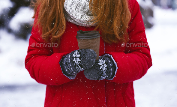 Woman holding paper cup with hot drink over winter background - Stock Photo - Images