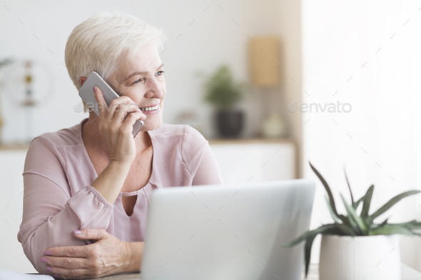 Positive old woman talking by phone with clients - Stock Photo - Images