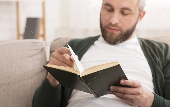 Close up of bearded man reading book at home - Stock Photo - Images