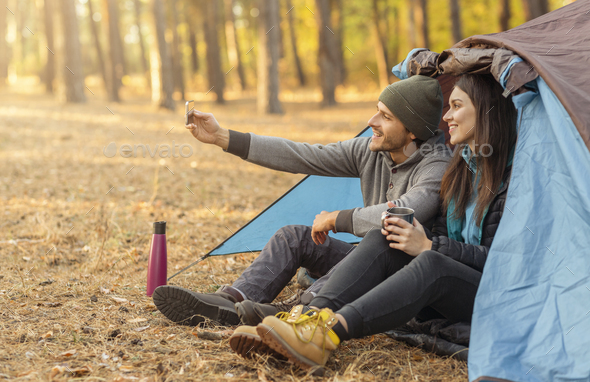 Couple of tourists taking selfie in camping tent - Stock Photo - Images