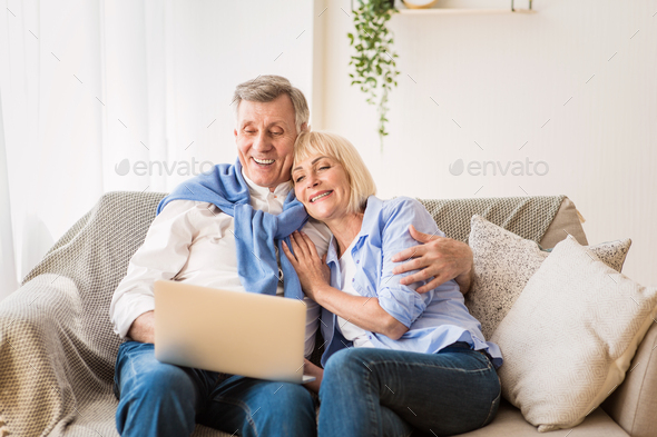 Mature man and his wife working with laptop at home - Stock Photo - Images
