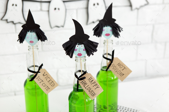 Close up of paper witches heads on the top of glass bottles - Stock Photo - Images