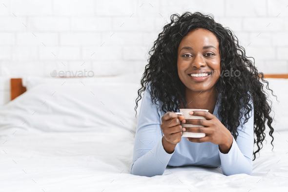 Happy girl relaxing in bed with cup of coffee - Stock Photo - Images