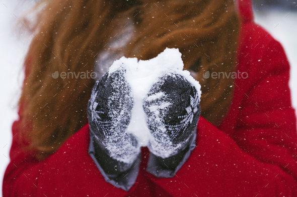 Cropped image of girl holding snowball with warm gloves - Stock Photo - Images