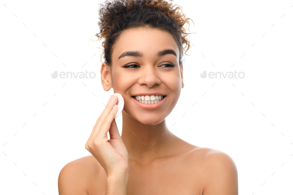Black girl cleaning her face with cotton sponge - Stock Photo - Images