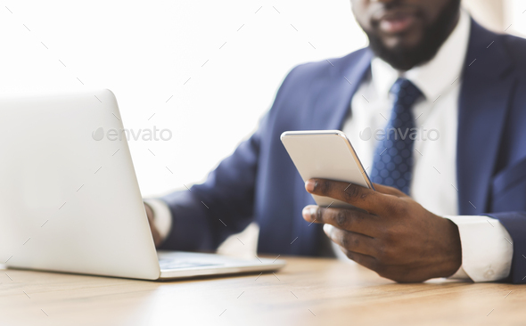 Close up of businessman using cellphone at workplace - Stock Photo - Images