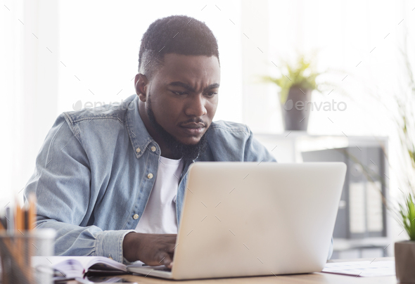 Focused african american employee working on laptop in office - Stock Photo - Images