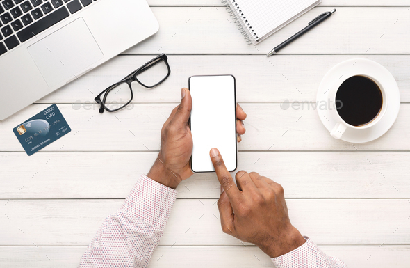 Black hands using smartphone with blank screen at workplace - Stock Photo - Images