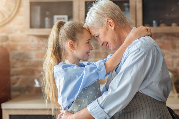Little granddaughter hugging her happy grandmother in kitchen - Stock Photo - Images