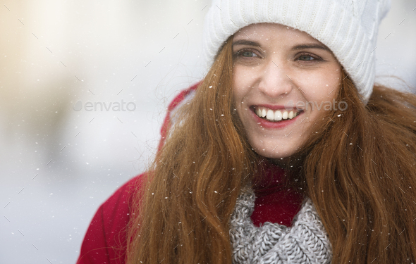 Close up portrait of beautiful ginger girl over snowfall - Stock Photo - Images