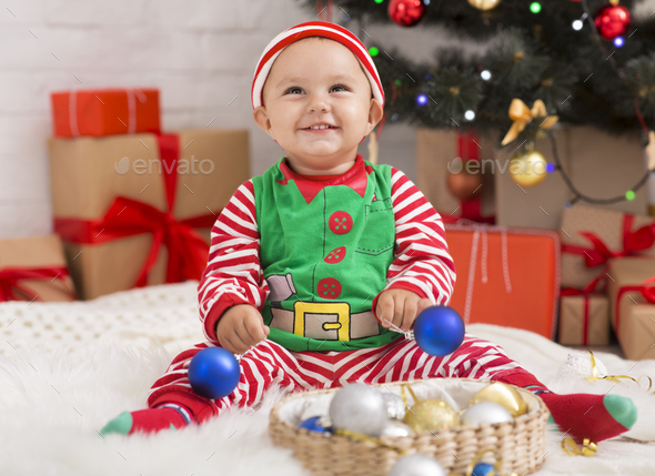 Joyful baby playing with Christmas decorations under xmas tree - Stock Photo - Images