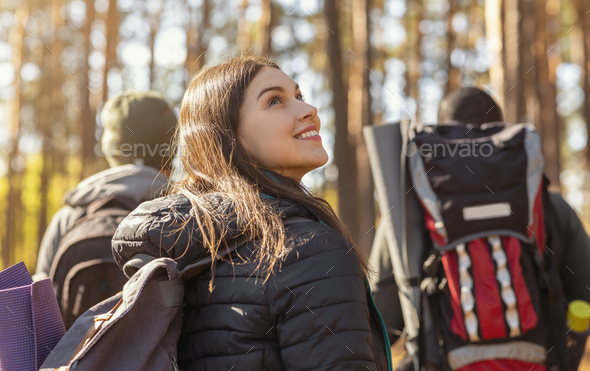 Three tourists hiking in autumn woods, girl looking around - Stock Photo - Images