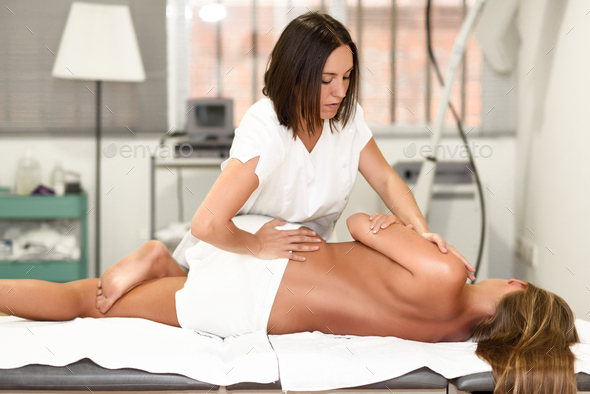 Professional female physiotherapist giving shoulder massage to blonde woman - Stock Photo - Images