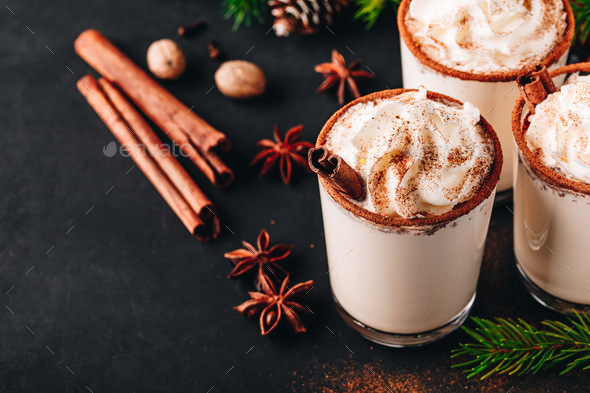 Traditional Christmas drink Eggnog with whipped cream and cinnamon on dark stone background. - Stock Photo - Images