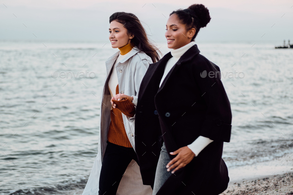 Beautiful positive stylish girls in trench coats happily holding each other hands walking by the sea - Stock Photo - Images