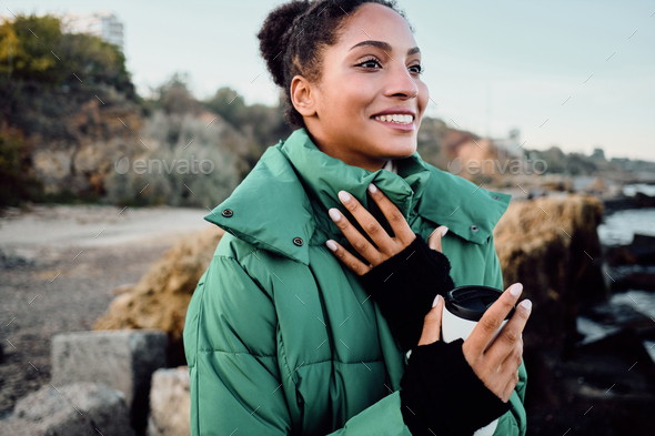 Pretty cheerful African American girl in down jacket with cup to go happily looking away on seaside - Stock Photo - Images