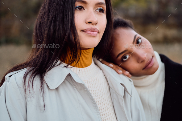 Attractive African American girl intently looking in camera standing with pretty Asian friend - Stock Photo - Images