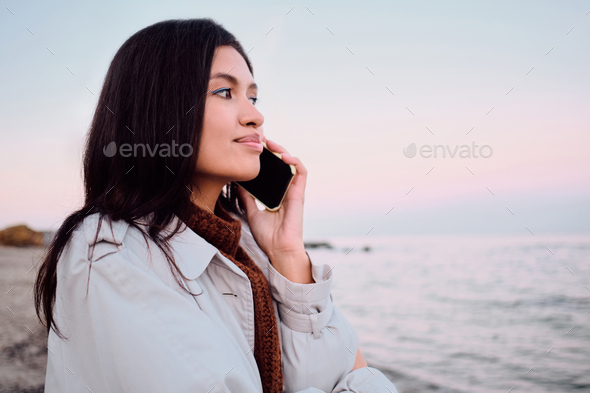 Side view of pretty Asian brunette girl dreamily talking on cellphone by the sea - Stock Photo - Images