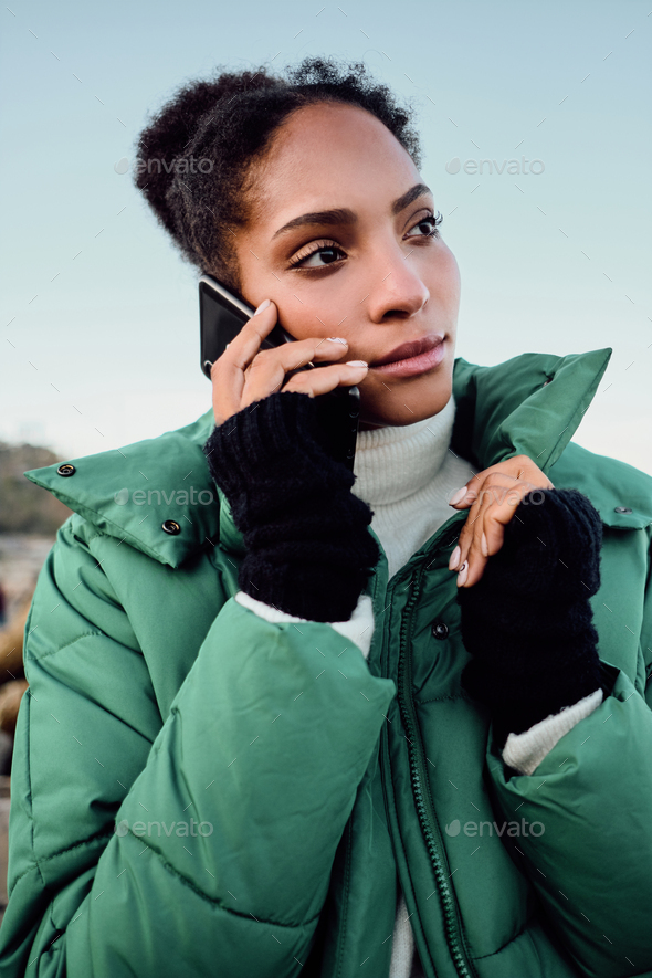 Pensive African American girl in down jacket thoughtfully talking on cellphone by the sea - Stock Photo - Images