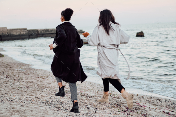 Back view of two attractive stylish girls in trench coats happily running by the sea - Stock Photo - Images