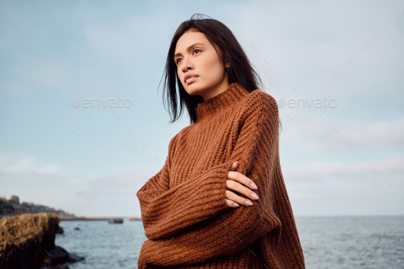 Gorgeous Asian brunette girl in cozy knitted sweater sensually looking away on seaside - Stock Photo - Images