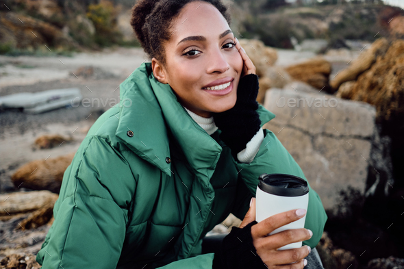 Attractive smiling African American girl in down jacket with cup to go happily looking in camera - Stock Photo - Images