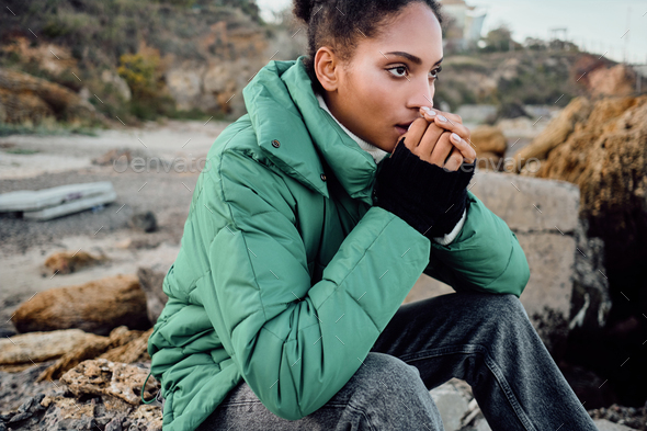 Beautiful stylish African American girl in down jacket warming hands sitting on stones outdoor - Stock Photo - Images
