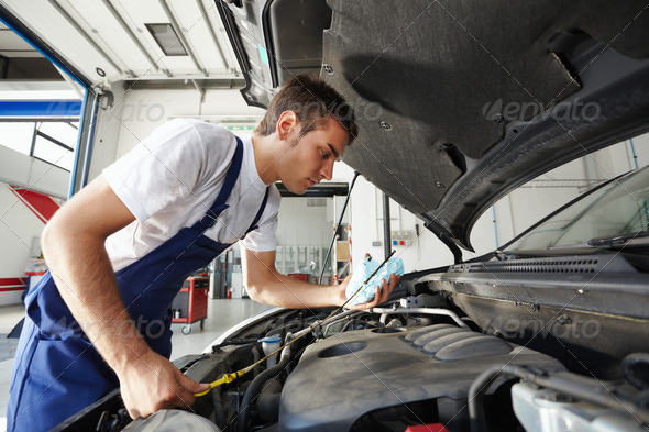 Man Working In Car Repair Shop As Mechanic Reviewing Engine Oil - Stock Photo - Images