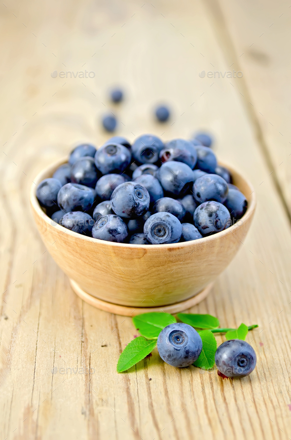Blueberries in a wooden bowl on the board - Stock Photo - Images