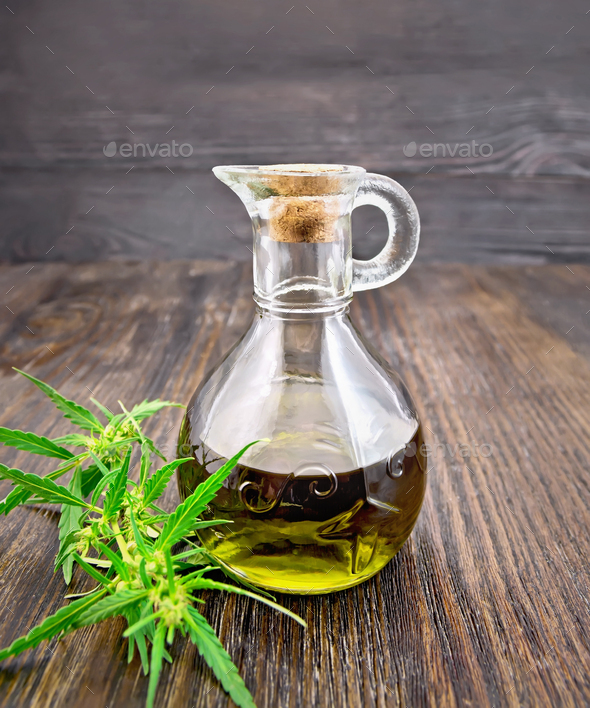 Oil hemp in glass decanter on dark board - Stock Photo - Images